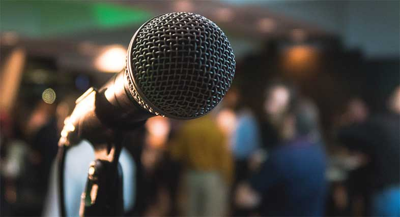 Microphone in front of a crowd - Photo by Kane Reinholdtsen on Unsplash
